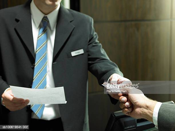 Mature businessman giving credit card at hotel reception