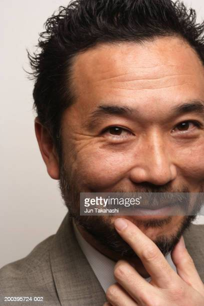 Mature businessman, hand on chin, smiling, close-up, portrait