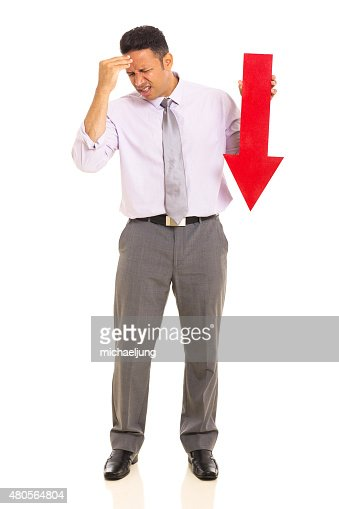 mature businessman holding arrow pointing down : Stock Photo