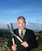 Mature businessman holding hedge shears, portrait