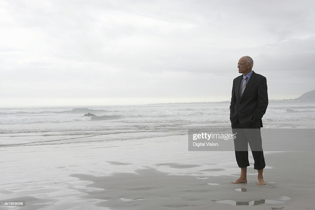 Mature Businessman in a Suit Stands on a Beach at the Water's Edge, Looking Out to Sea