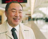 Mature businessman in airport, smiling