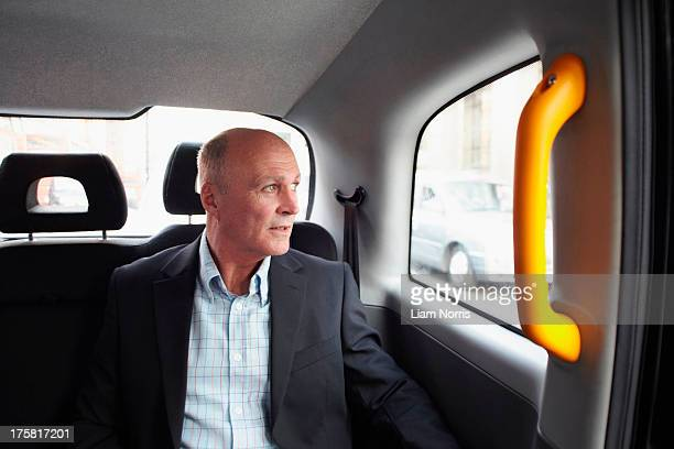 Mature businessman in black cab, London, England, UK