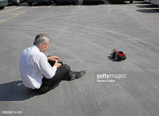 Mature businessman in car park, playing with radio controlled car