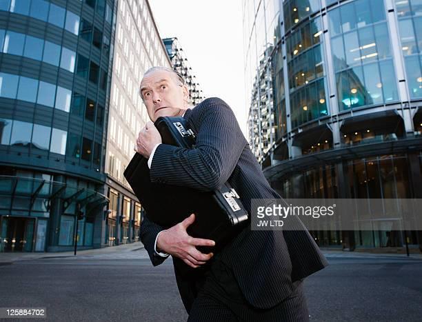 Mature businessman in city clutching briefcase