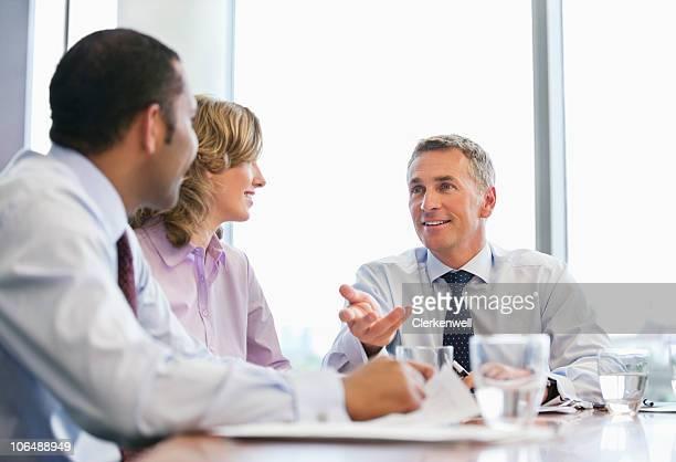 Reifer Geschäftsmann, im Gespräch mit Kollegen im Meetingraum