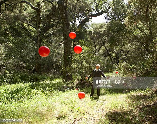 Mature businessman in woods with red balls