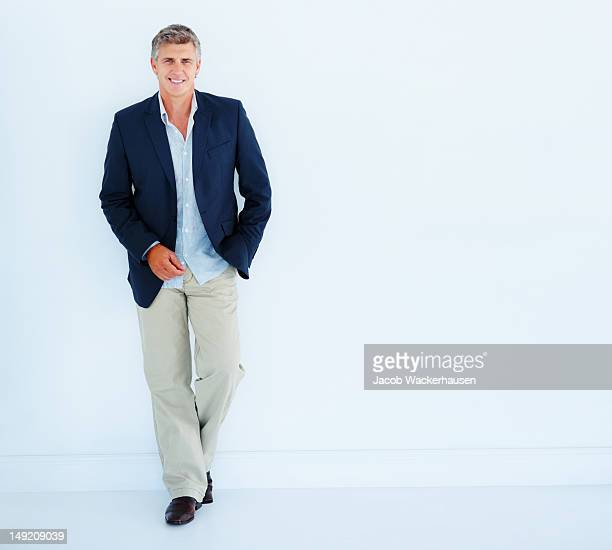 Mature businessman leaning against white background