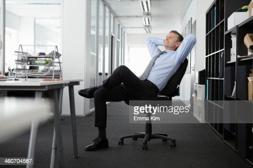 Mature businessman leaning back in office chair