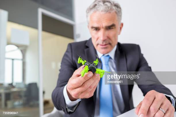 Mature businessman looking at drone