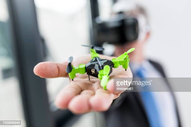 Mature businessman looking at drone through VR goggles