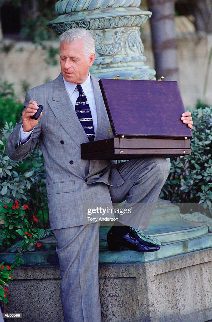 Mature businessman looking at pager