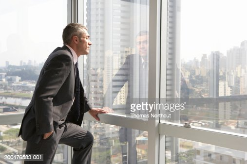 Mature businessman looking out office window, side view : ストックフォト
