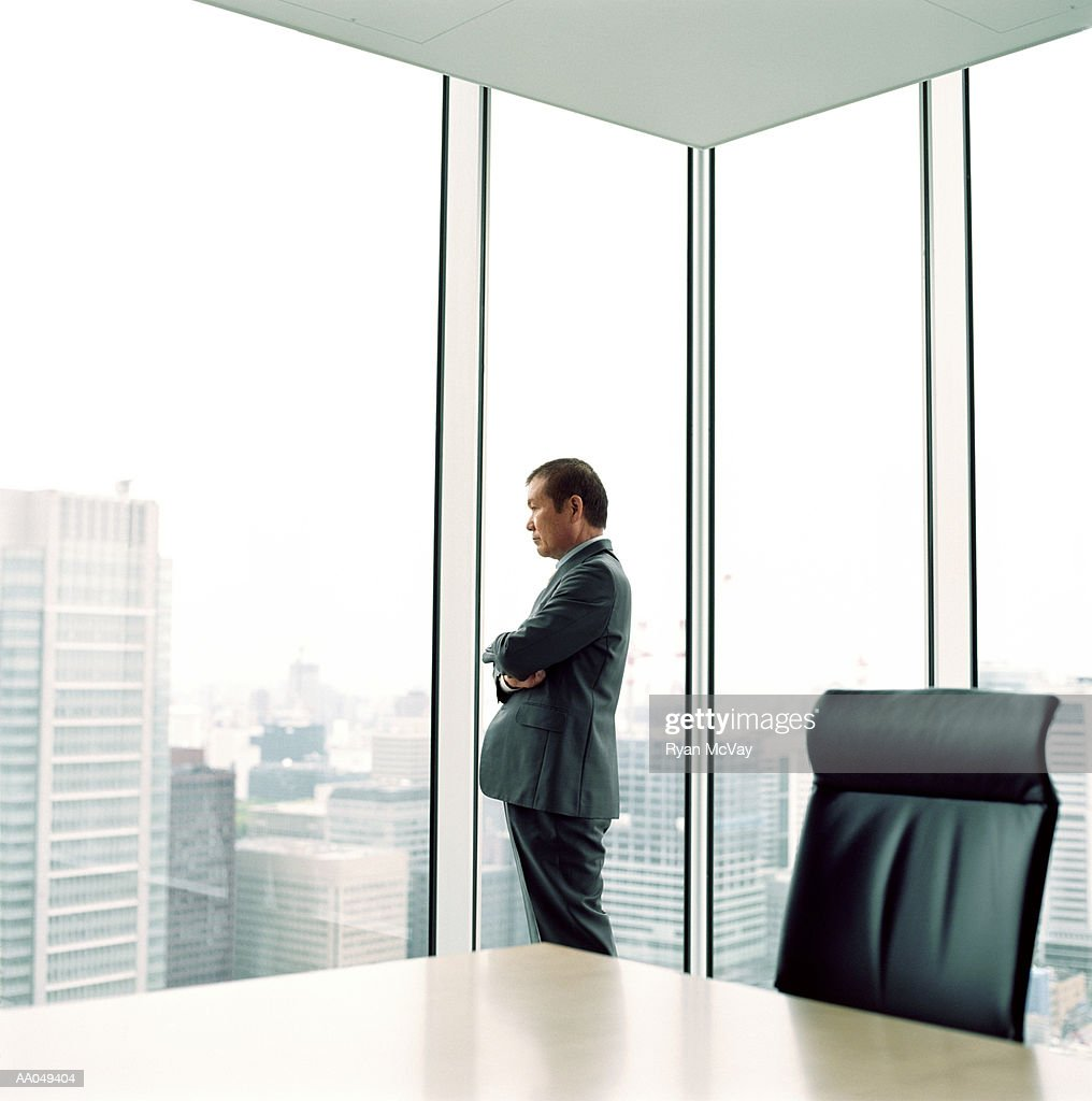 Mature businessman looking out office window, side view : Stock Photo