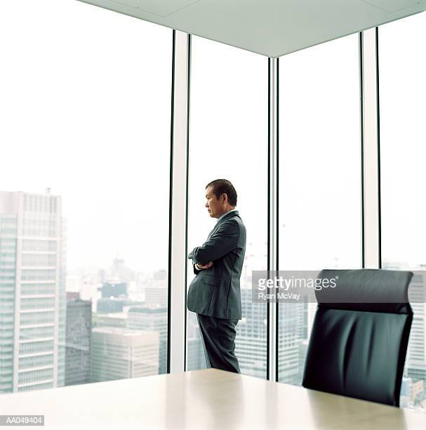 Mature businessman looking out office window, side view