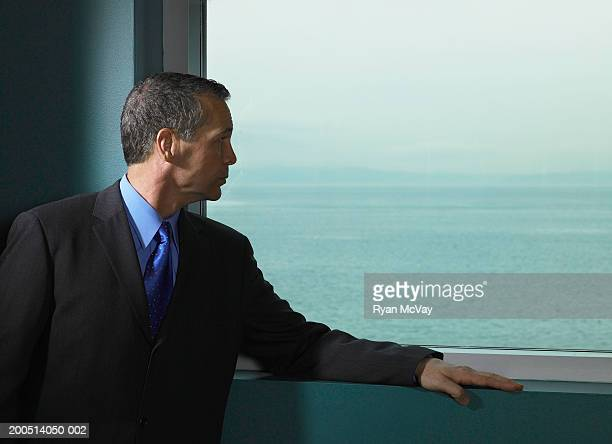Mature businessman looking out window out across seascape
