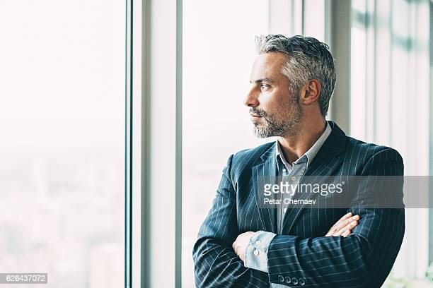 Mature businessman looking through the window