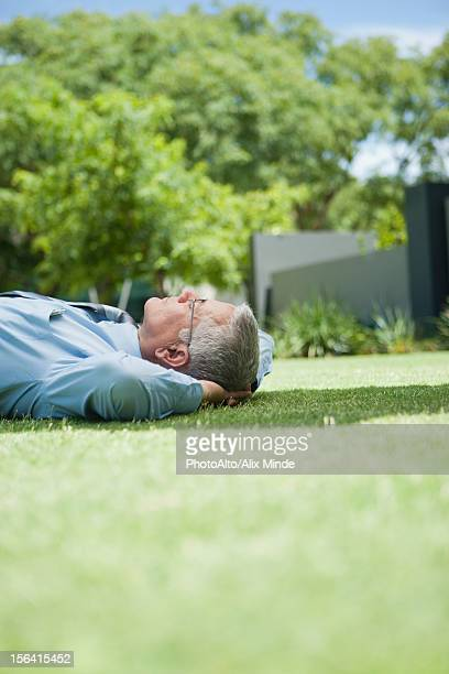 Mature businessman napping on grass