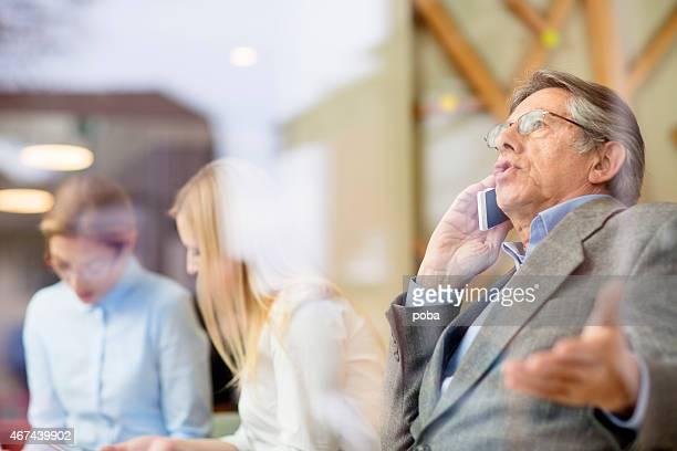 Reifer Geschäftsmann am Telefon, während in seinem Büro arbeiten