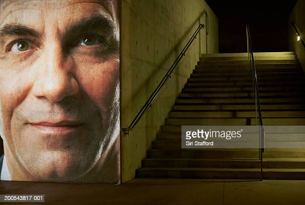 Mature businessman projected along cement wall by staircase