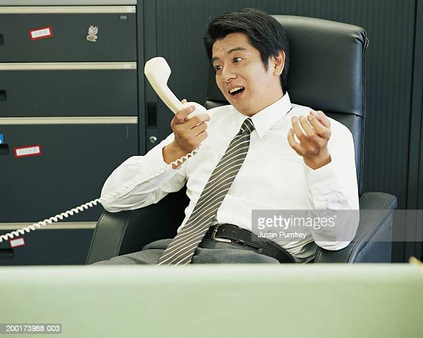 Mature businessman pulling facial expression at telephone receiver