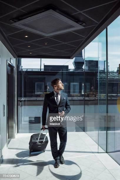 Mature businessman pulling wheeled luggage in hotel corridor