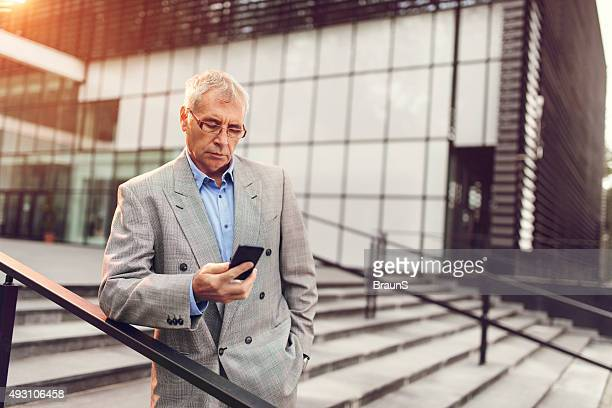 Mature businessman reading a text message on mobile phone outdoors.