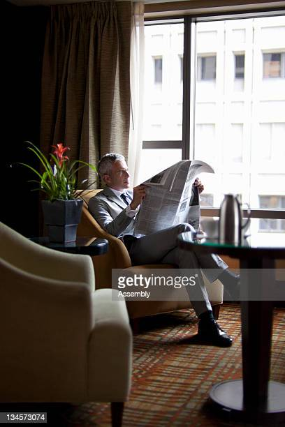 Mature businessman reading newspaper in lounge