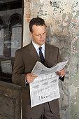 Mature businessman reading newspaper