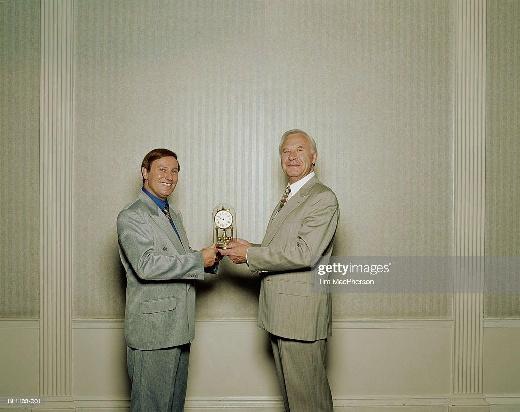 Mature businessman receiving clock from male colleague, portrait : Stock Photo