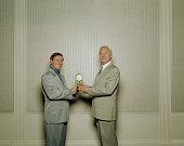 Mature businessman receiving clock from male colleague, portrait