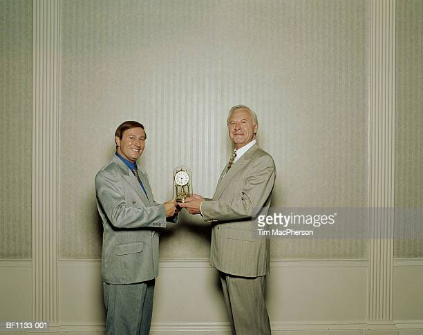 Mature businessman receiving clock from male colleague, portrait