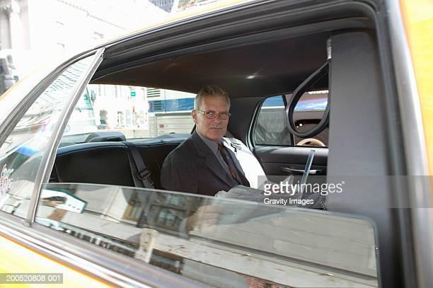 Mature businessman riding in taxi, portrait