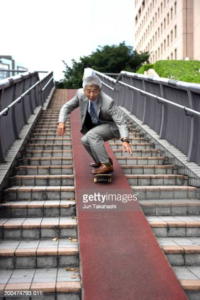 Mature businessman riding skateboard down stairway, low angle view