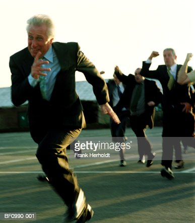 Mature businessman running from crowd outdoors (blurred motion)