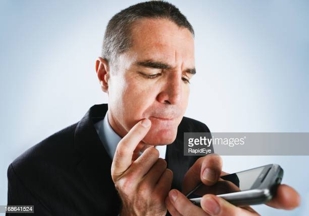 Mature businessman seems confused by his cell phone