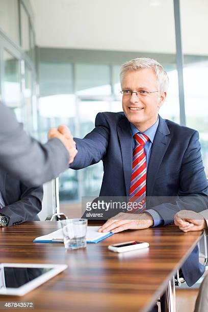Reifer Geschäftsmann beim Händeschütteln mit einem Kollegen