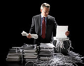 Mature businessman shredding documents