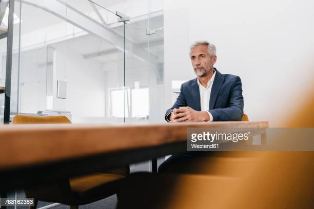 Mature businessman sitting at conference table in office