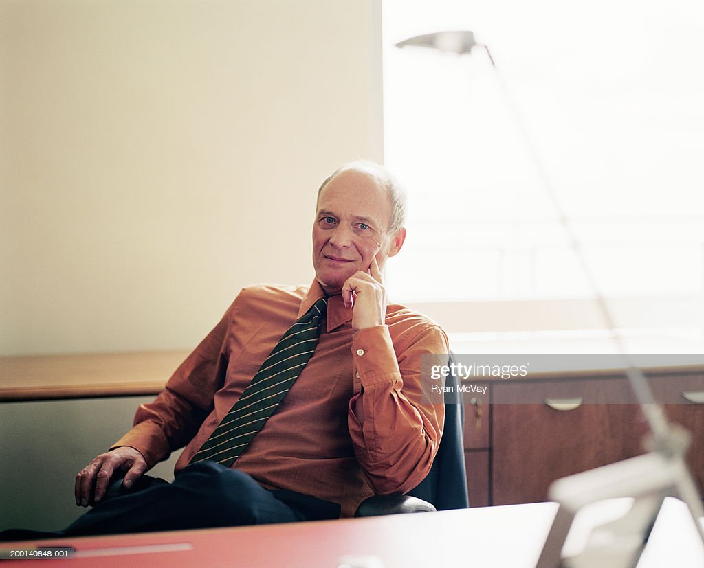 Mature businessman sitting at desk, portrait