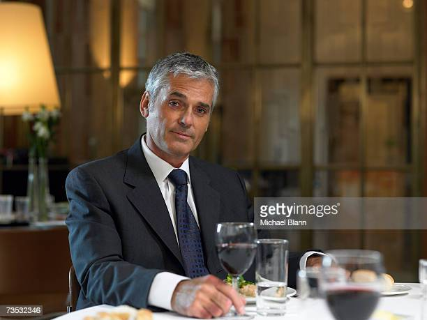 Mature businessman sitting at restaurant table, holding wineglass