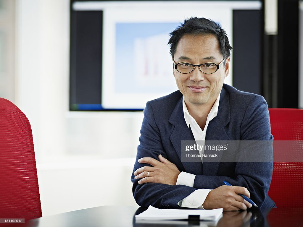 Mature businessman sitting at table arms crossed : Stock Photo