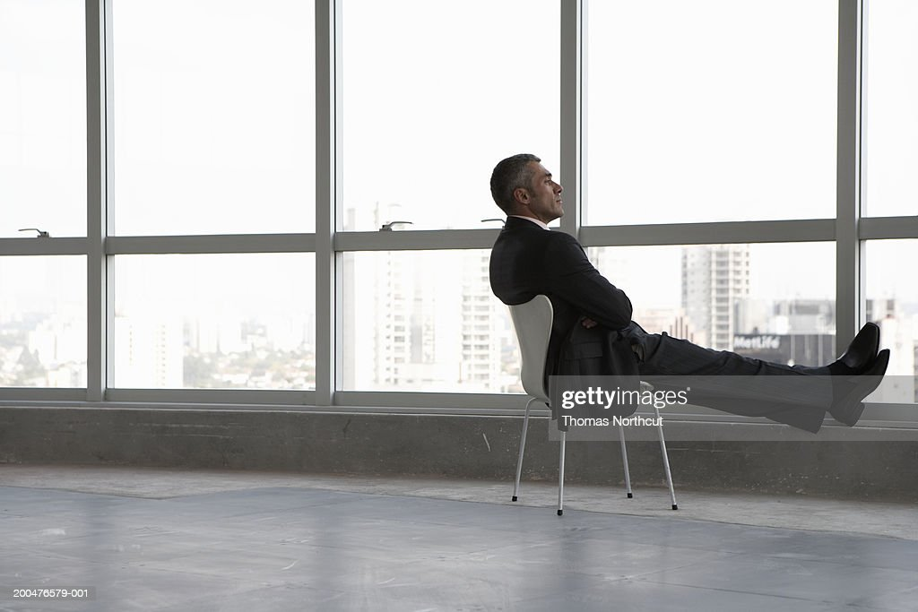 Mature businessman sitting beside window in empty building, side view : Stock Photo