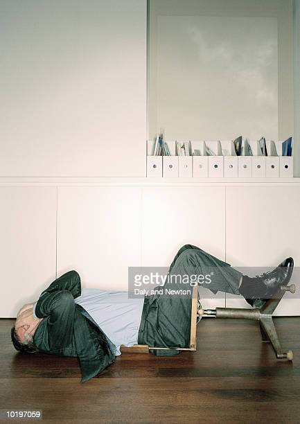 Mature businessman sitting in overturned chair, hands on head