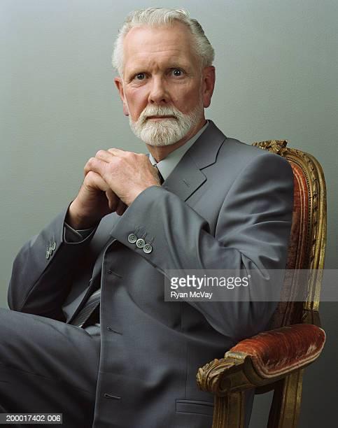 Mature businessman sitting on chair, portrait