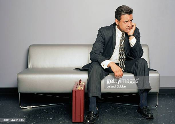 Mature businessman sitting on couch, hand to chin