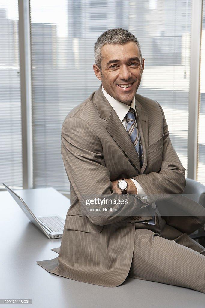 Mature businessman sitting on desk, arms crossed, smiling, portrait : Stock Photo
