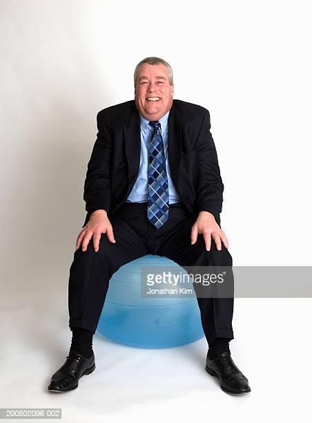 Mature businessman sitting on exercise ball, smiling, portrait