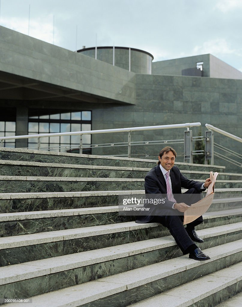 Mature businessman sitting on steps with newspaper, portrait : Stock Photo