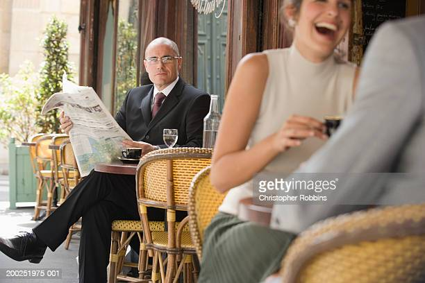 Mature businessman sitting outside cafe looking up from newspaper